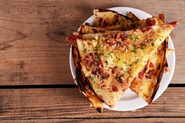Saborosas fatias de pizza no prato na mesa de madeira