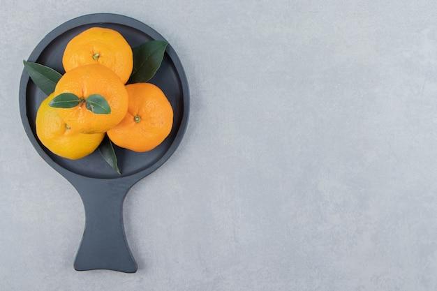 Saborosas frutas de clementina em quadro negro
