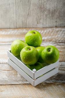 Saborosas maçãs verdes em uma caixa de madeira na luz de madeira e fundo do grunge.