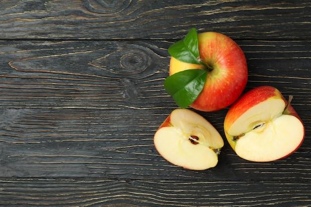 Saborosas maçãs vermelhas maduras na mesa de madeira
