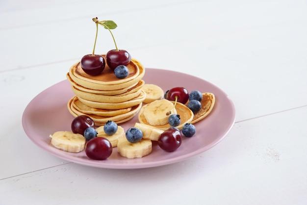 Saborosas panquecas caseiras com frutas frescas no prato violeta. saudável café da manhã de panquecas com mirtilos, cerejas e bananas.
