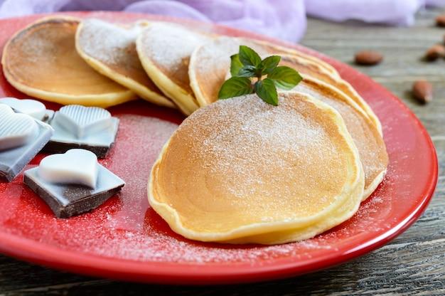 Saborosas panquecas com açúcar de confeiteiro em um prato vermelho sobre uma mesa de madeira. sobremesa festiva sobre o tema do amor. fechar-se