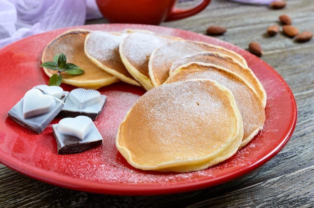 Saborosas panquecas com açúcar de confeiteiro em um prato vermelho sobre uma mesa de madeira. sobremesa festiva sobre o tema do amor.