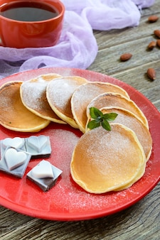 Saborosas panquecas com açúcar de confeiteiro em um prato vermelho sobre uma mesa de madeira