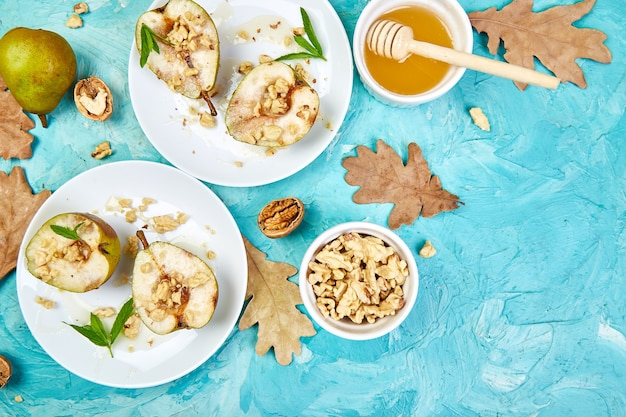 Saborosas peras assadas com mel e nozes na mesa de fundo azul.