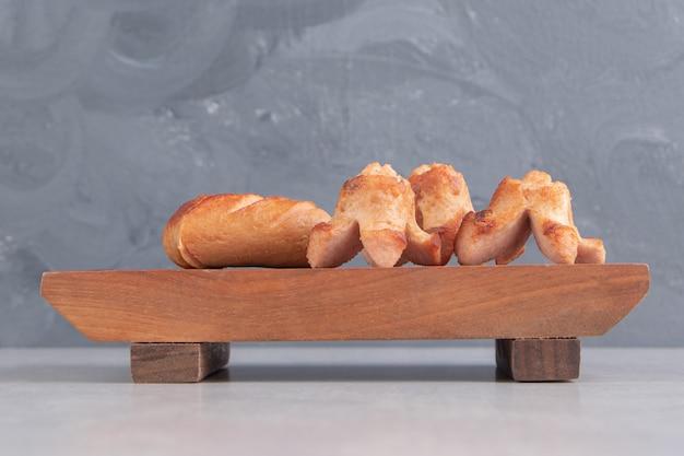 Saborosas salsichas grelhadas na placa de madeira.