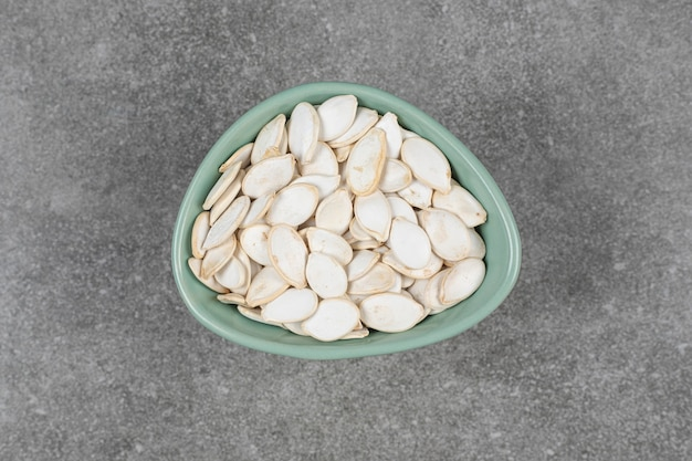 Saborosas sementes de abóbora em uma tigela azul.