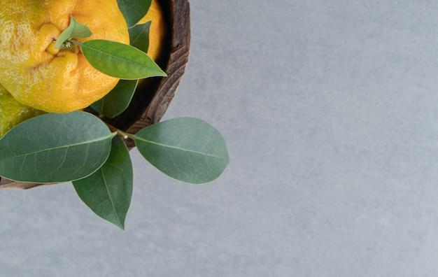 Saborosas tangerinas empilhadas em um balde de madeira no mármore.