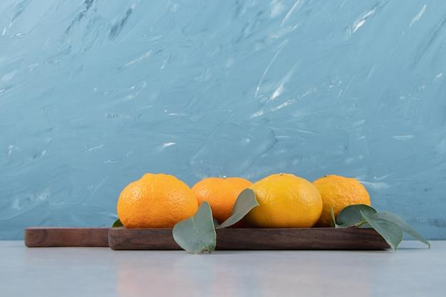 Saborosas tangerinas frescas em tábua de madeira