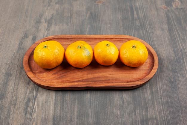 Saborosas tangerinas ou tangerinas em uma placa de madeira. foto de alta qualidade