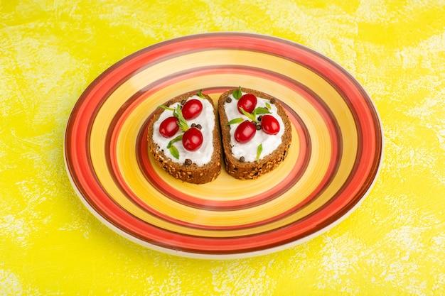 Saborosas torradas de pão com creme de leite e dogwoods dentro de um prato laranja em amarelo