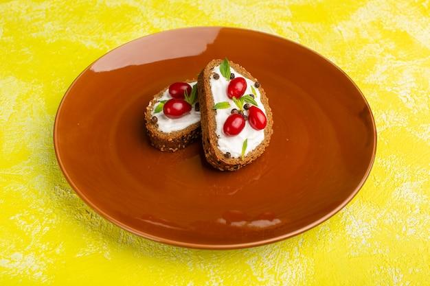 Saborosas torradas de pão com creme de leite e dogwoods dentro de um prato marrom sobre amarelo