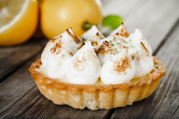 Saborosas tortinhas de merengue de limão com hortelã na velha mesa de madeira
