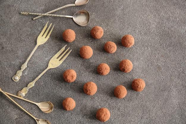 Saborosas trufas doces com talheres em cinza