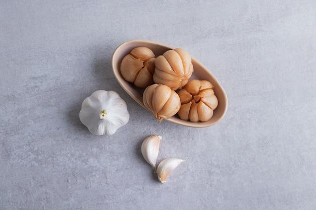 Saboroso alho em conserva na tigela colocada na mesa de pedra.