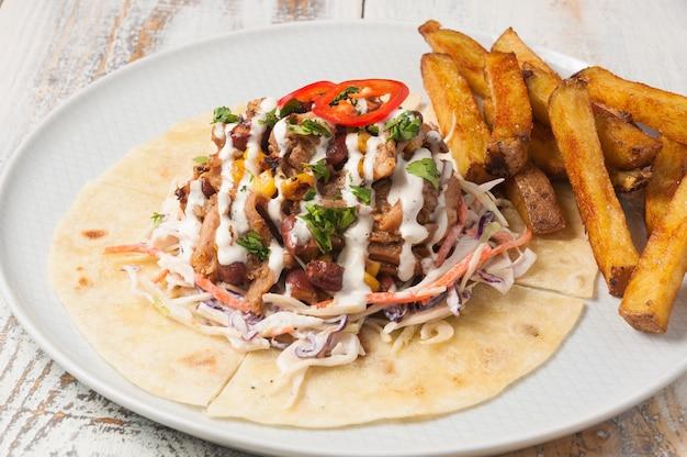 Saboroso almoço com carne e vegetais em tortilhas e batatas fritas