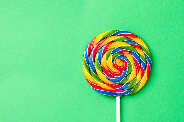 Saboroso apetitoso acessório para festa sweet swirl candy lollypop no fundo verde vista superior