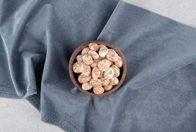 Saboroso biscoito de canela na tigela sobre a toalha, na superfície de mármore