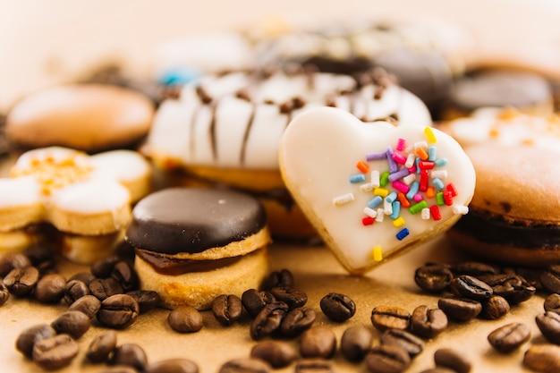 Saboroso biscoito em forma de coração entre biscoitos e grãos de café