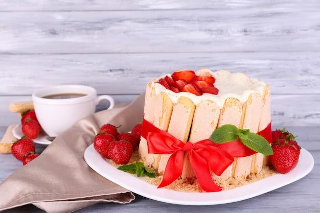Saboroso bolo charlotte com morangos frescos na mesa de madeira