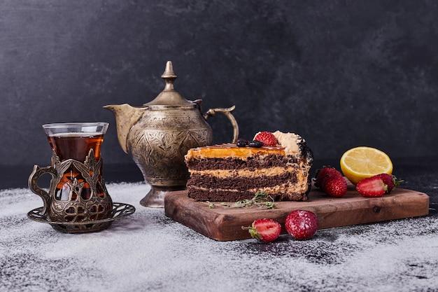 Saboroso bolo de chocolate com jogo de chá e frutas em fundo escuro.