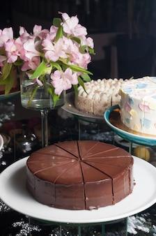 Saboroso bolo de chocolate sacher em fundo escuro com flores cor de rosa