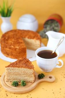 Saboroso bolo de mel caseiro em fundo amarelo com uma xícara de café, leite e flores