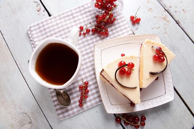 Saboroso bolo de queijo com frutas e uma xícara de chá na mesa close-up