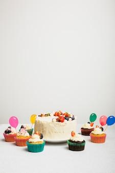Saboroso bolo fresco com frutas e conjunto de bolinhos