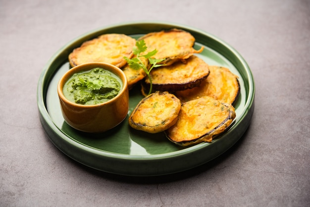 Saboroso brinjal pakora ou bolinhos crocantes de berinjela, lanche da hora do chá indiano servido com chutney verde