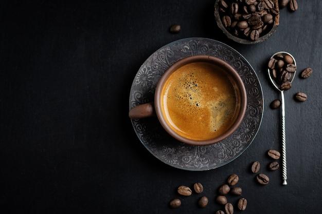 Saboroso café americano na xícara com grãos de café