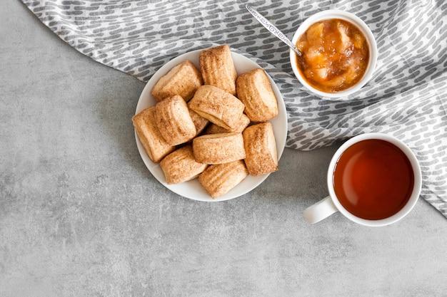Saboroso café da manhã. biscoitos doces de canela caseiros, xícara de chá e confeito de maçã