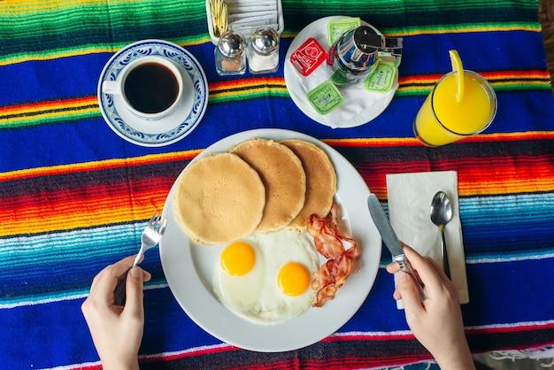 Saboroso café da manhã com panquecas, ovos fritos e bacon na mesa.