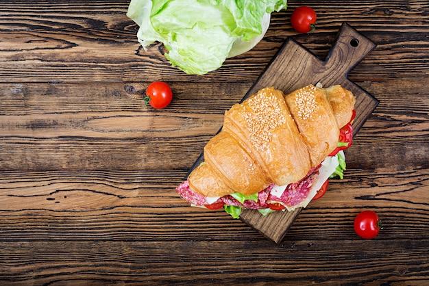 Saboroso café da manhã. croissant apetitoso com salame e queijo e tomate. postura plana. vista do topo