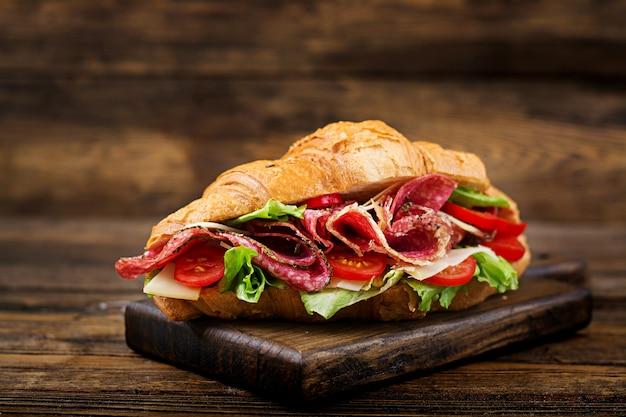 Saboroso café da manhã. croissant apetitoso com salame e queijo e tomate