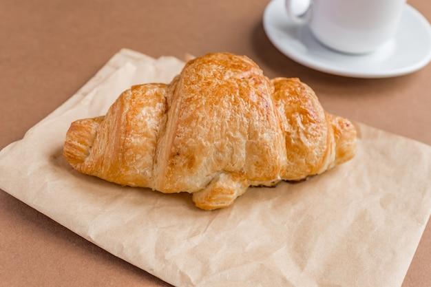 Saboroso café da manhã. croissant francês servido na chapa branca e xícara de café preto ou café sobre fundo marrom. copie o espaço.