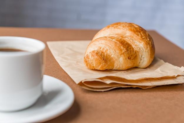 Saboroso café da manhã. croissant francês servido no papel do ofício e xícara de café preto ou café expresso em fundo marrom. bandeira