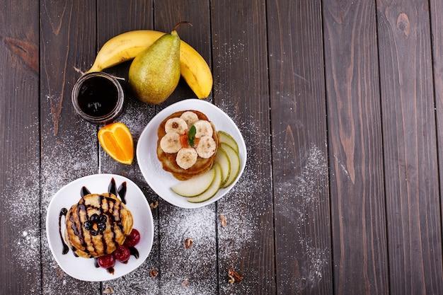 Saboroso café da manhã. deliciosas panquecas cobertas com chocolate, cerejas, bananas e peras