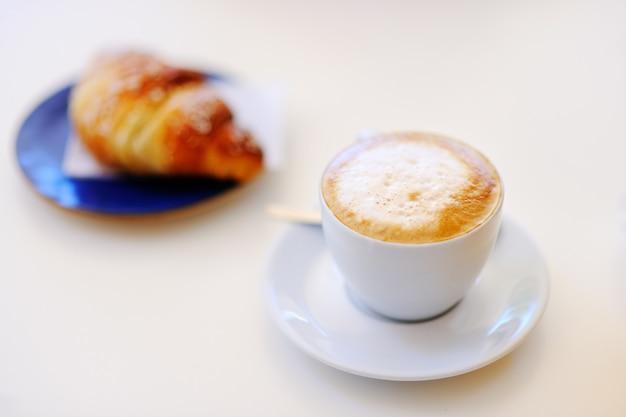 Saboroso café da manhã em um café de rua italiano - xícara de café e croissant na mesa branca