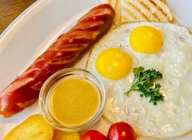 Saboroso café da manhã, ovos fritos com salsicha e mostarda doce em um prato. estilo leigo plano. vista do topo