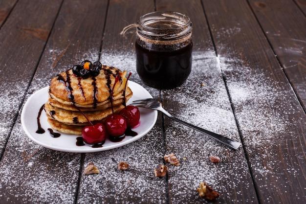 Saboroso café da manhã. panquecas deliciosas cobertas com chocolate e cerejas