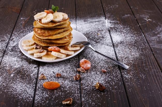Saboroso café da manhã. puncakes deliciosos com bananas, nozes e hortelã, servido na chapa branca