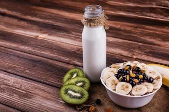 Saboroso café da manhã saudável feito de leite e mingau com nozes, kiwis e mel