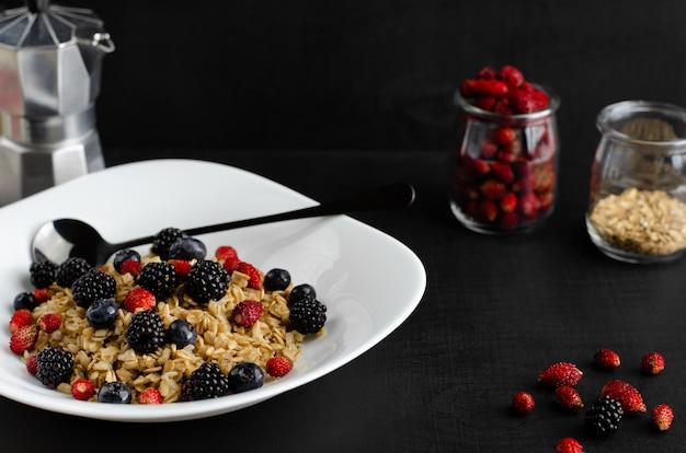 Saboroso café da manhã saudável. mingau de aveia com frutos silvestres em fundo escuro.