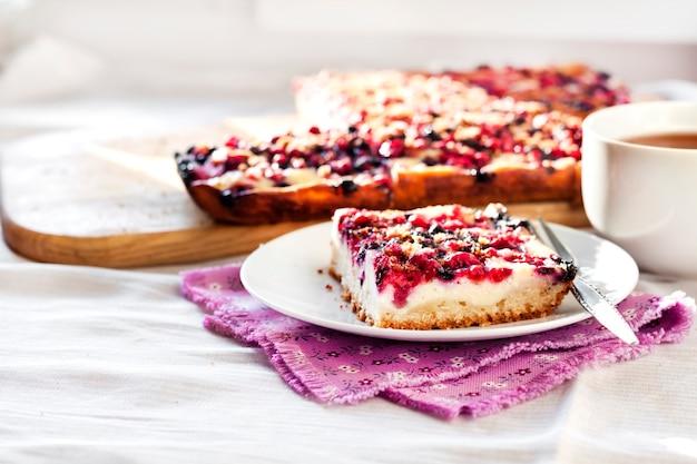 Saboroso café da manhã. torta deliciosa com frutas sortidas e queijo cottage e uma xícara de chá. copie o espaço