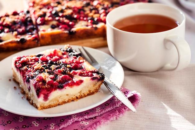 Saboroso café da manhã. torta deliciosa com frutas variadas e queijo cottage e uma xícara de chá