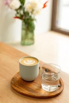 Saboroso cappuccino quente na mesa de madeira ao lado da janela