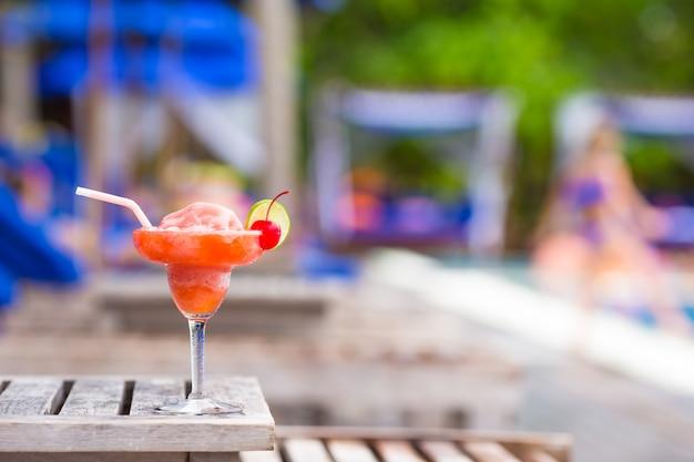 Saboroso cocktail na mesa de madeira perto da piscina