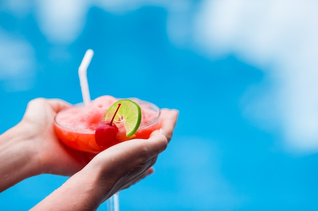 Saboroso cocktail no mar turquesa de mãos femininas