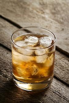 Saboroso colorido frio álcool beber uísque com gelo no vidro na mesa de madeira.